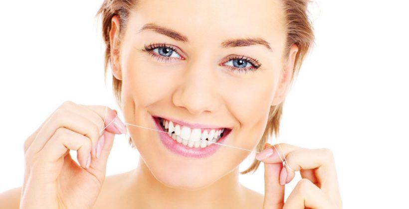 Chica usando hilo dental